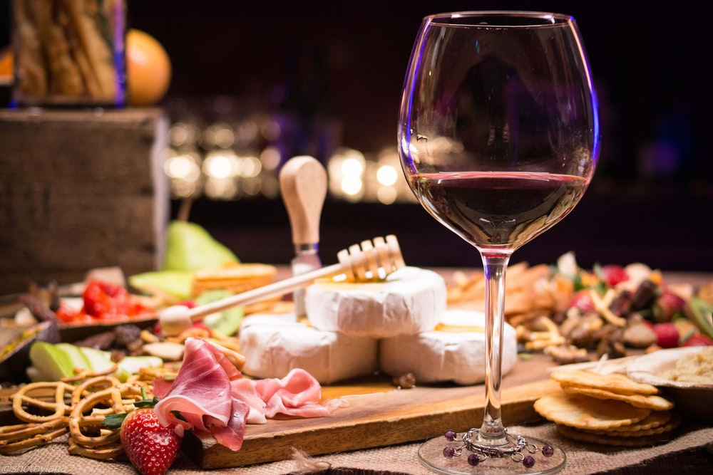 clear wineglass near brown wooden board